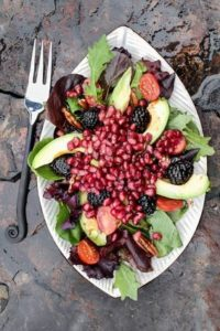 A healthy salad with pomegranate, avocado, tomatoes, almonds and argula lettuce over a rustic background.
